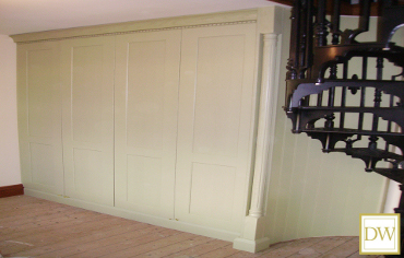 Painted 'English Green 'oak wardrobes with curved tongue & groove paneling & feature pilaster.