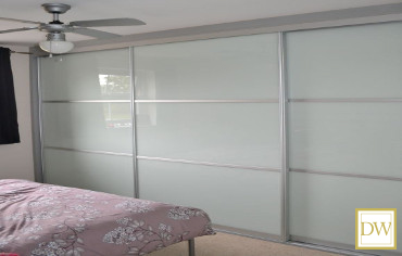 Bespoke quality glass sliding doors in soft white with complimentary aluminium trim.